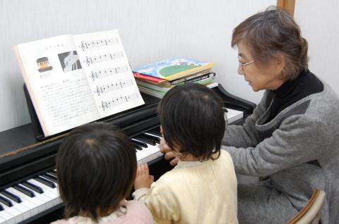 幼児たちにピアノを教えるエリー