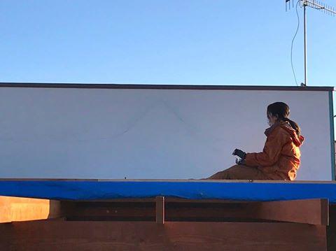 テラスの上の壁に壁画を描くひとみちゃん